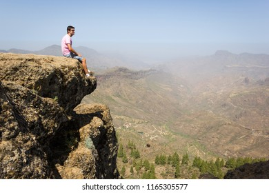Lonely tourist on pink t shirt sitting on edge of cliff rock. Young man staring at natural beauty in Roque Nublo national park, Spain. Risk, danger, confident, dare, courage, vertigo, no fear concepts