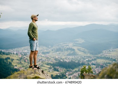 Lonely traveler man in summer clothes standing on stone at top of carpathian mountain and looking far from high altitude. Nature landscape with far horizon. Tourist resting in wild terrain on vacation