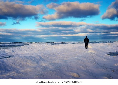 Lonely traveler on the snow-covered coast of the frozen sea in the evening