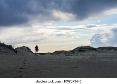 Lonely traveler watching the sunset on the top of a sand dune in the Curionian Spit, Lithuania