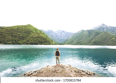lonely traveler woman meditates looking at a spectacular mountain view with the lake