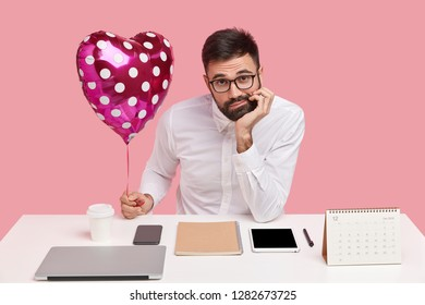 Lonely unshaven male holds chin, has discontent expression, holds valentine, wears white shirt, has clueless look, sits at workplace with gadgets, being perfectionist, isolated against pink background