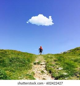 Lonely walker in a mountain path under a single cloud