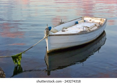 A lonely white boat tied with a rope