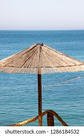Lonely wicker sun umbrella at mediterranean beach by sea. Natural bamboo sunshades and summer umbrella parasol on ocean beach. Large straw beach umbrellas against blue water and sky. Vacation, travel.