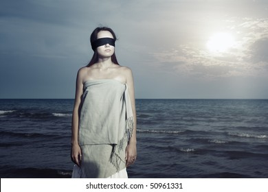 Lonely woman with blindfold listening waves of the sea during sunset. Special colors and processing in artistic manner