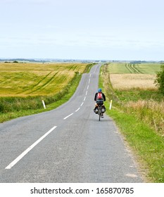 Lonely woman cycle tourist on the scenic countryside road in Denmark.