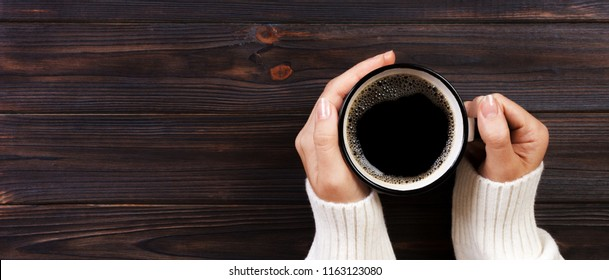 Lonely woman drinking coffee in the morning, top view of female hands holding cup of hot beverage on wooden desk. Banner.