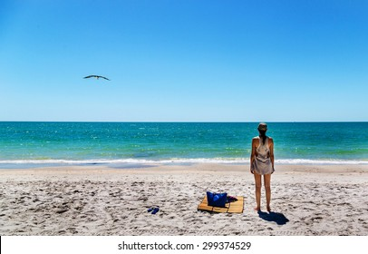 Lonely woman enjoying a blue sea in Naples, Florida,