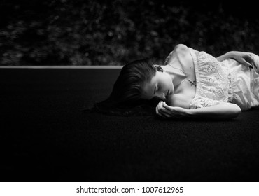 Lonely woman lie on the road with closed eyes in a white dress. Depression. Black and white photo