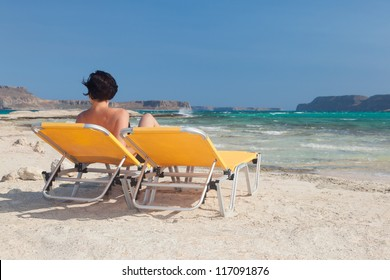 Lonely woman on an empty beach. White sand. Blue sky. Nobody. Free space. Two orange chaise. Woman without man.
