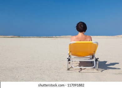 Lonely woman on an empty beach. White sand. Blue sky. Nobody. Free space. Orange chaise.