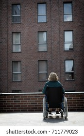 lonely woman on wheelchair surrounded by bricked buildings, dark moody tones