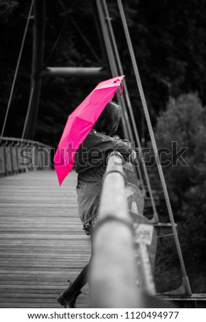 336c35f2834 Lonely woman in the rain with a pink umbrella standing on the steel bridge  in monochrome black and white - Image