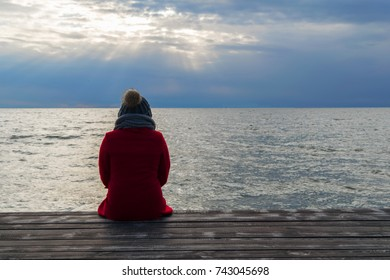 Lonely woman in red woolen coat, gray scarf and hat with pompom is seating on wooden dock and looking on sunset over ocean.