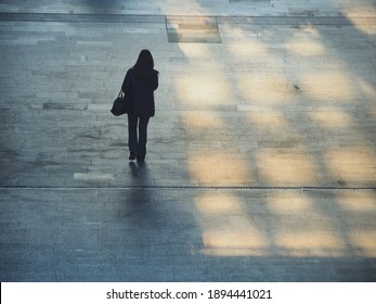 Lonely woman silhouette walking in train station view from behind