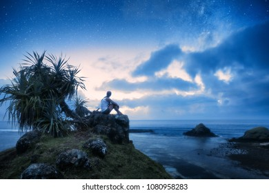 A lonely woman sits on the seashore and looks at the starry sky