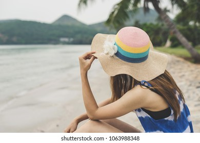 Lonely woman sitting absent minded and looking at the sea