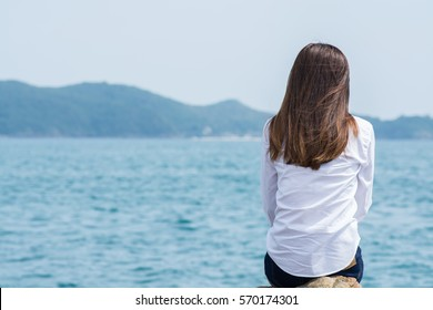Lonely woman sitting alone on a rock at sea