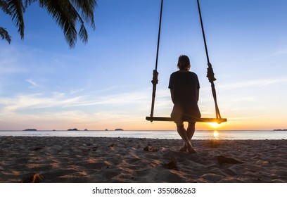 Lonely woman sitting on a rope swing at sunset watching at the sea and thinking about life