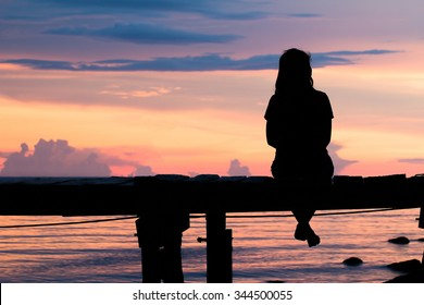 Lonely woman sitting on a wooden bridge sunset.are Lonely. style abstract shadows.silhouette