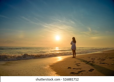 Lonely woman standing on beach sunrise time.