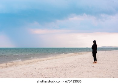 Lonely woman standing on the beach.