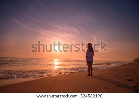 lonely woman standing on beach sunset の写真素材 今すぐ編集