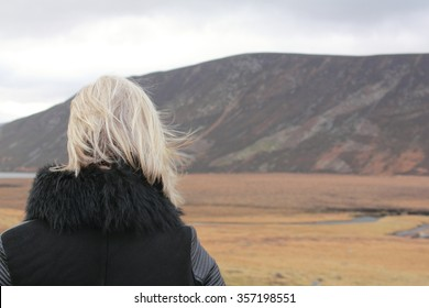 A lonely woman stares into space over a wide open space