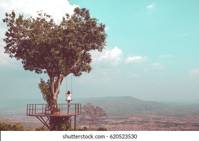 "Lonely woman swing on giant tree and mountain background at ""Noen-Maprang"" ,Phitsanulok Province,Thailand. Vintage concept."