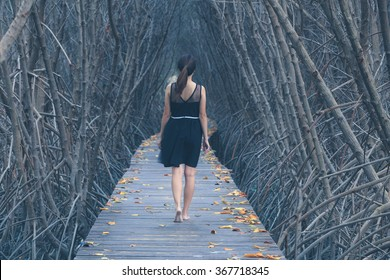 lonely woman walking alone on wooden bridge into the forest