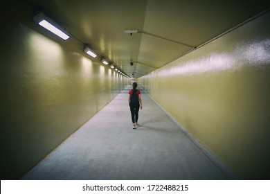 a lonely woman walking along a long underground tunnel