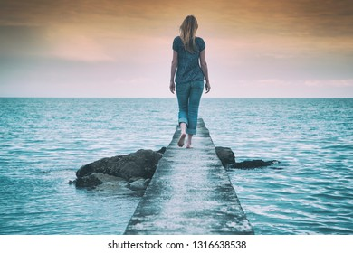 Lonely woman walking on the concrete pier at the sea.