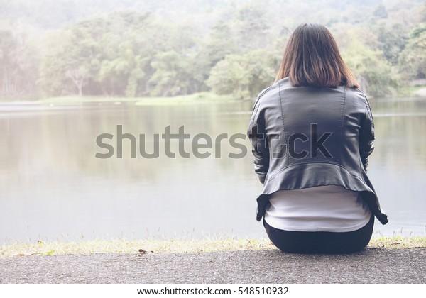 Einsame Frauen tragen eine schwarze Jacke und sitzen am Urlaubsmorgen auf dem Reservoir.