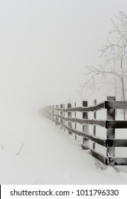 Lonely wooden fense winding in winter snow