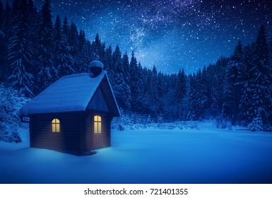Lonely wooden house on a meadow in a deep forest covered with fresh snow. Majestic starry sky. Christmas winter night.