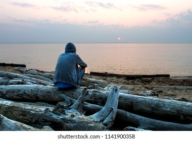 Lonely Young Man in a Hoodie sit on the Sea Background