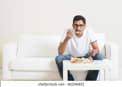 Lonely young single Indian man eating food alone, copy space at side. Having nasi lemak as lunch. Lifestyle of Asian guy at home.