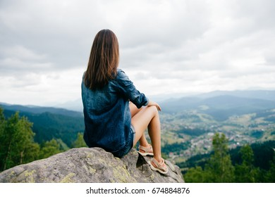 Lonely young traveler girl sitting on stone at top of mountain. Discovering new country. Beautiful nature landscape from high altitude. Summer trip on weekend vacation.  Edge of world. Jeans clothes.