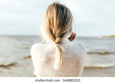 a lonely young woman by the sea looks into the distance
