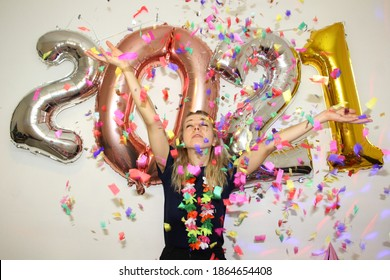 lonely young woman celebrating new year 2021 at home quarantine. lockdown. coronavirus crisis in end of 2020. 2021 starts. confetti falling. number balloons. girl with hads up. silvester party.
