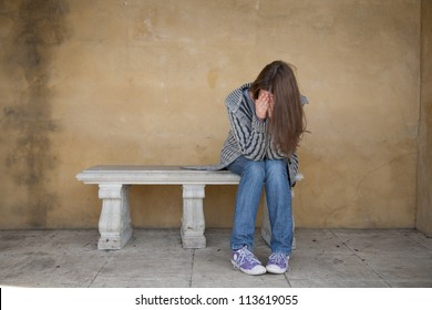 Lonely young woman crying on the bench