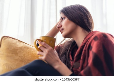 Lonely young woman feeling sad and worried, looking through a window, overthinking her problems and drinking tea