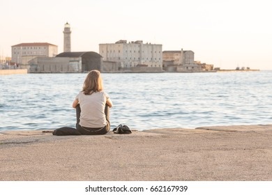 A lonely young woman seen from behind is sitting at the edge of a marina in Triest, Italy