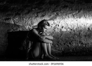 Lonely young woman sitting on the street, looking severely depressed. Black and white.