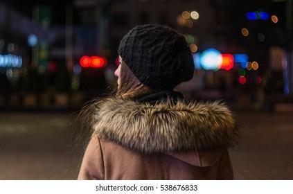 Joven solitaria caminando por la calle de la ciudad nocturna