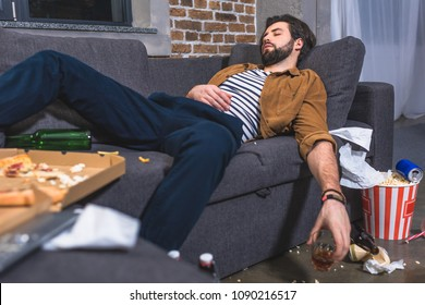 loner sleeping on sofa with glass of whiskey in dirty living room