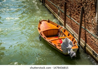 Lonesome motorboat with covered engine in a small canal in the lagoon city Venice in Italy at a sunny day in summer.