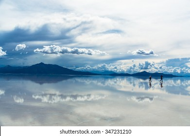 Lonesome Travelers being reflected in Salar de Uyuni, Bolivia