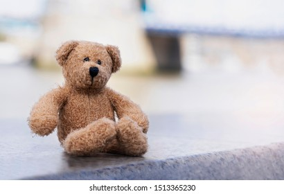Loney teddy bear sitting by the river, The forgotten bear sitting alone, lost property, Lonely concept, Lost child, International missing child